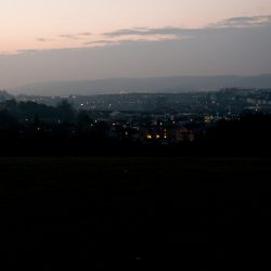 Dog walking at dusk. Twinkling lights seen from The Northern Slopes.